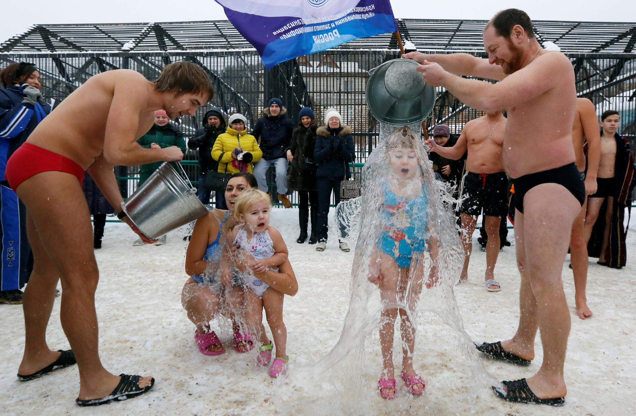 Membros do grupo Nadadores de Inverno despejam baldes de água gelada nas suas filhas de 2 e 7 anos, na cerimónia do dia do Urso Polar em Krasnoyarsk, Rússia, com a temperatura ambiente inferior a 5º C