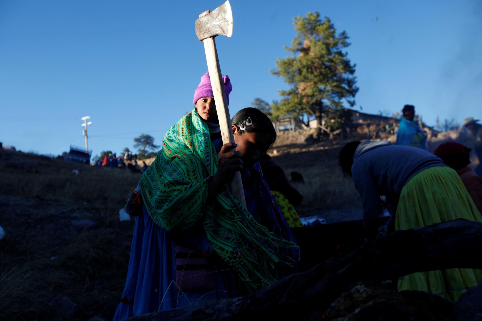 Na aldeia de Caborachi, México, uma mulher corta lenha para se preparar para o frio