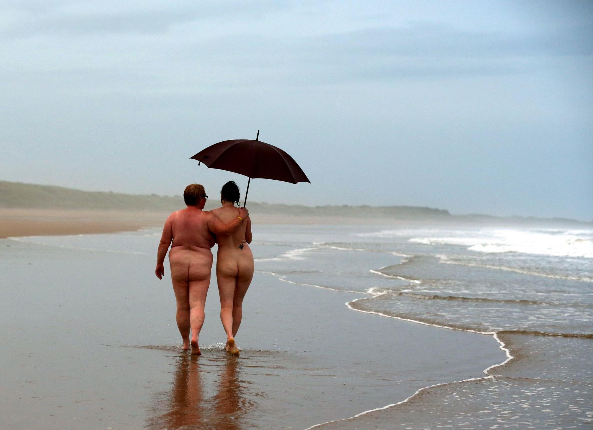 No evento anual <i>North East Skinny Dip</i>, centenas de nudistas mergulham na água fria do mar em Northumberland, Reino Unido