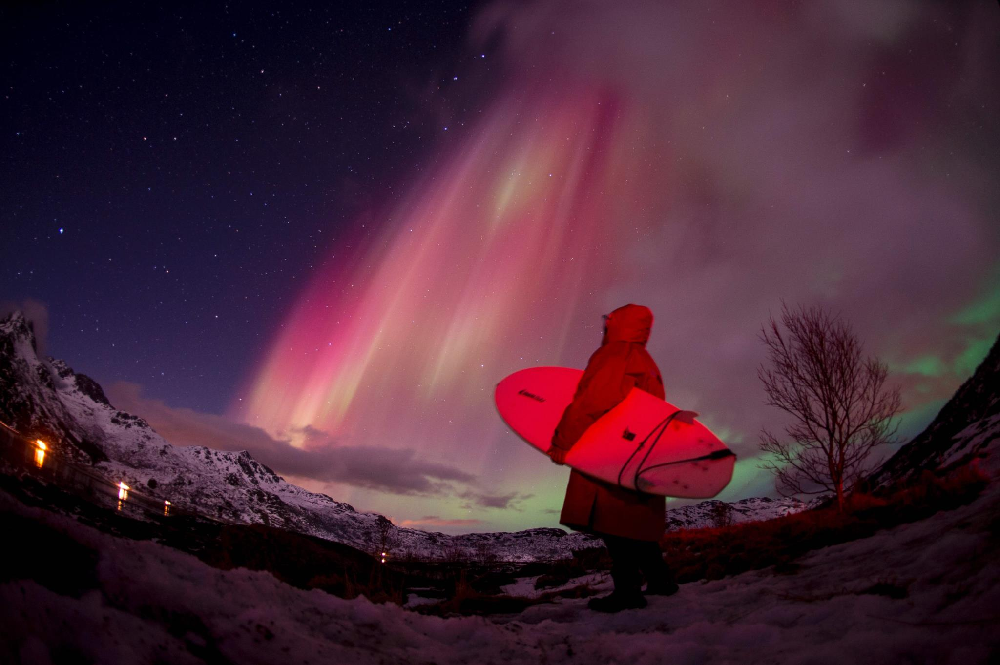 Um surfista observa as luzes da aurora boreal no arquipélago Lofoten, no Círculo Polar Árctico