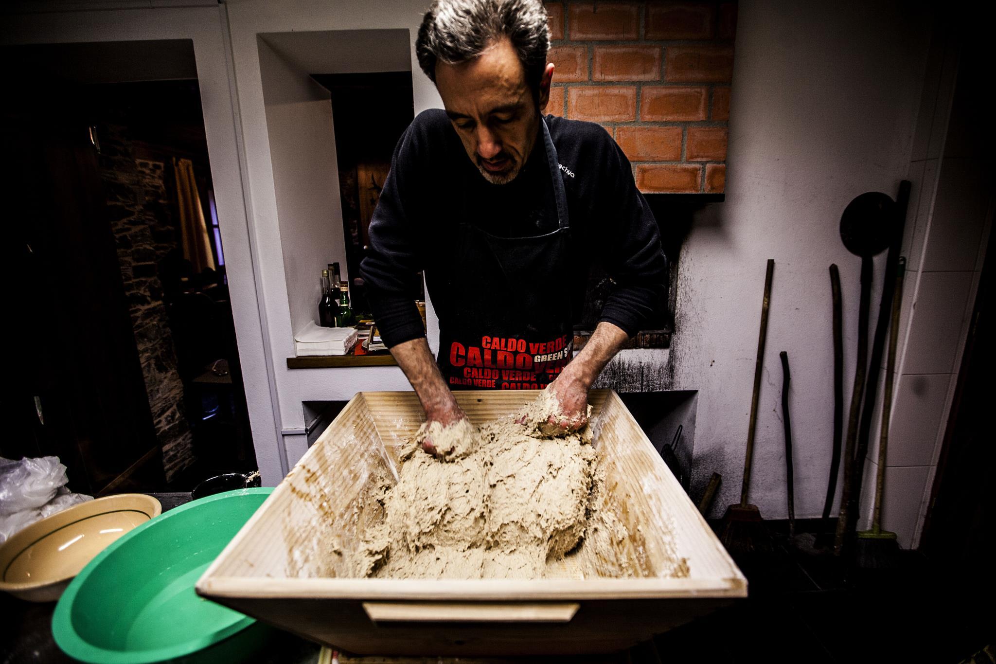 Mario Santos amassa o pão que vai a cozer no forno a lenha na Loja das Aldeias de Xisto