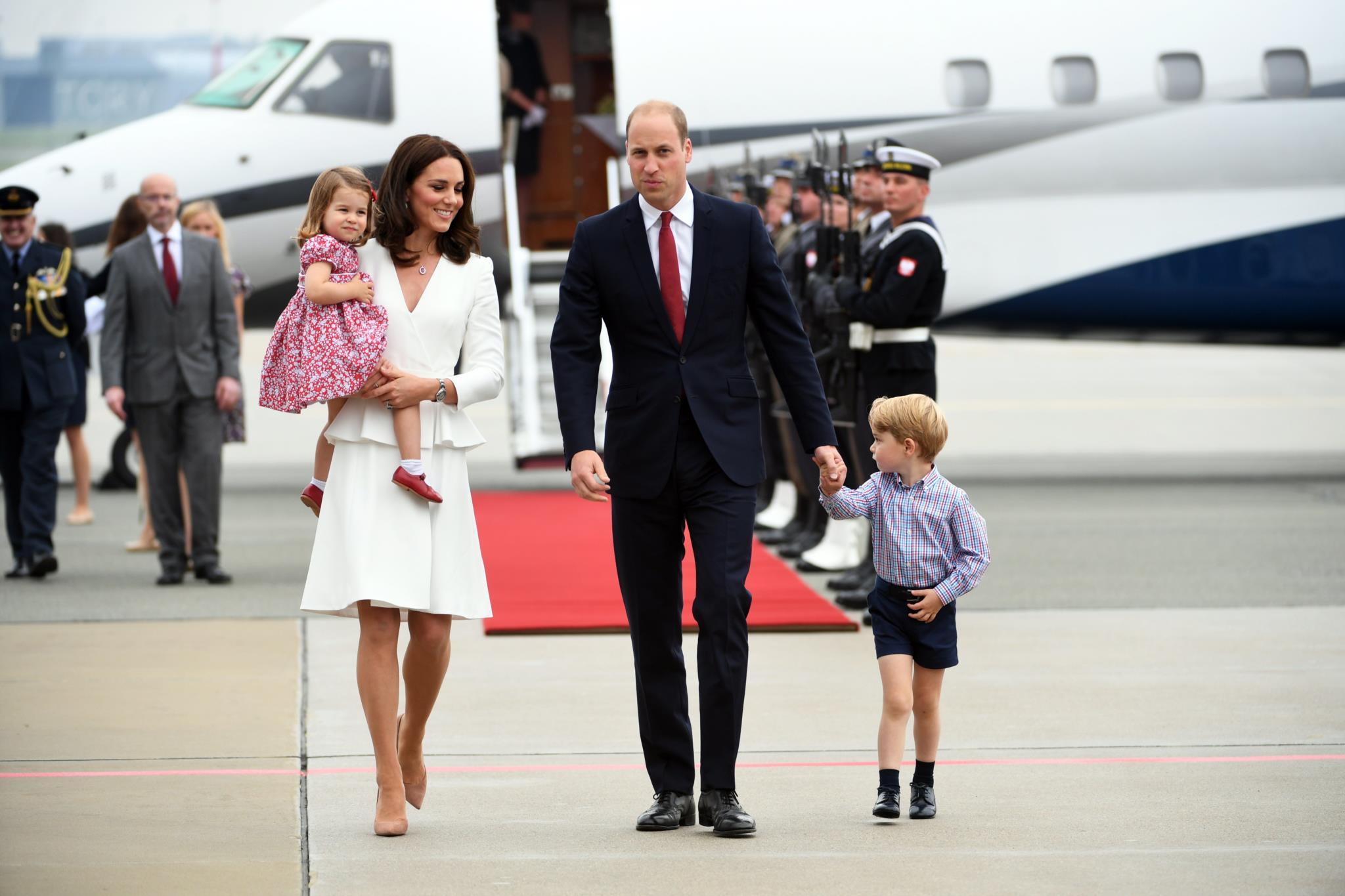 O diuque e a duquesa de Cambridge com os filhos à chegada ao aeroporto na Polónia