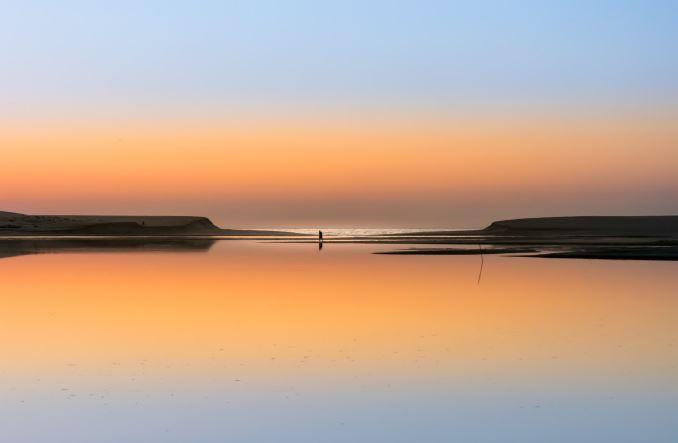 Alentejo: Na lagoa de Santo André, já com a lagoa aberta, Miguel aproveitou o final de tarde, e o facto de o céu se cruzar com a lagoa devido ao reflexo, para tirar a fotografia com os pescadores.