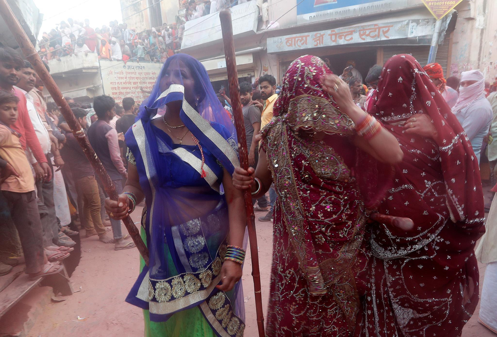 Mulheres indianas com varas de bambu nas celebrações do Festival das Cores