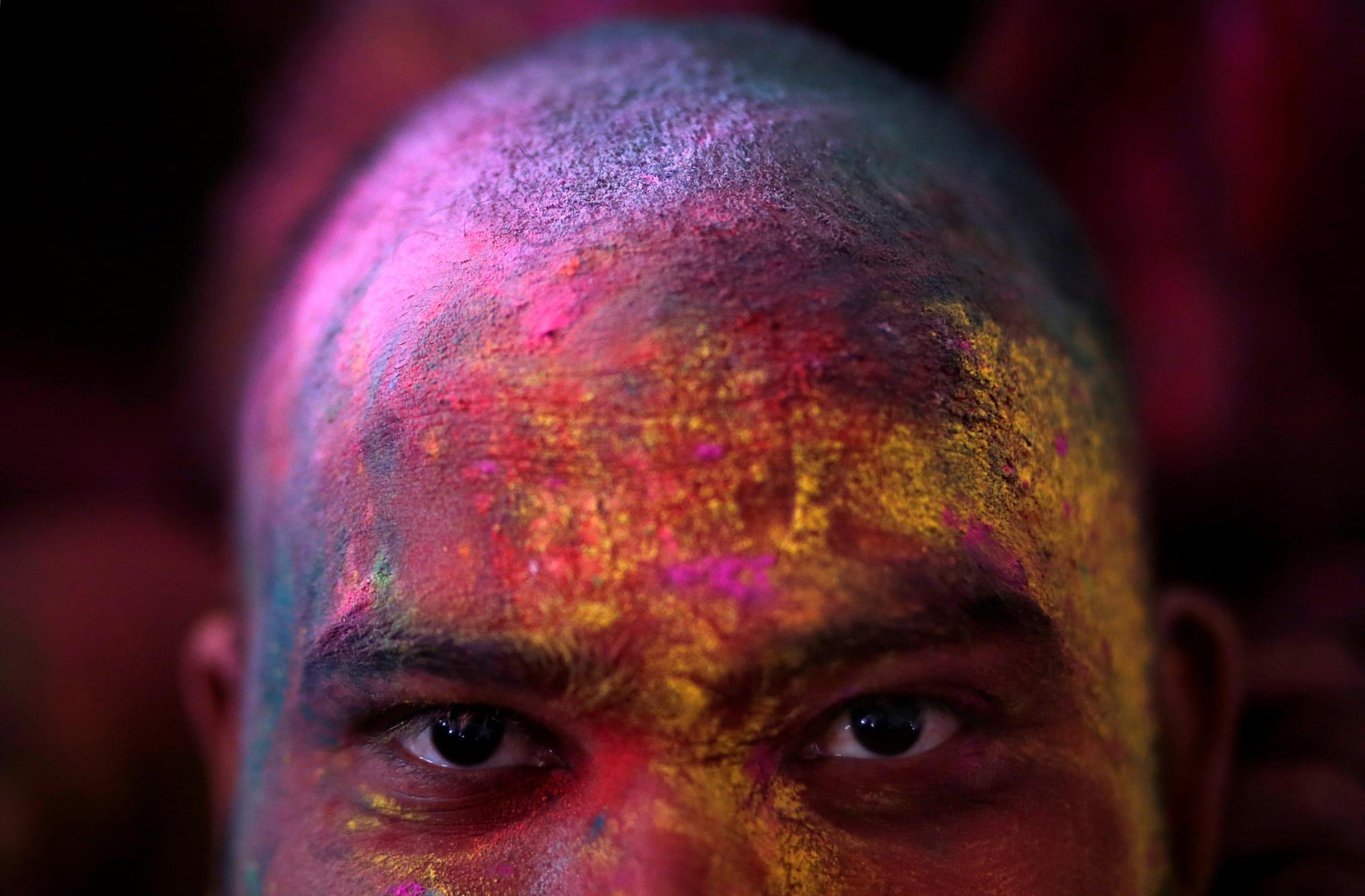 Um homem coberto de pós de várias cores durante o Festival das Cores na Índia