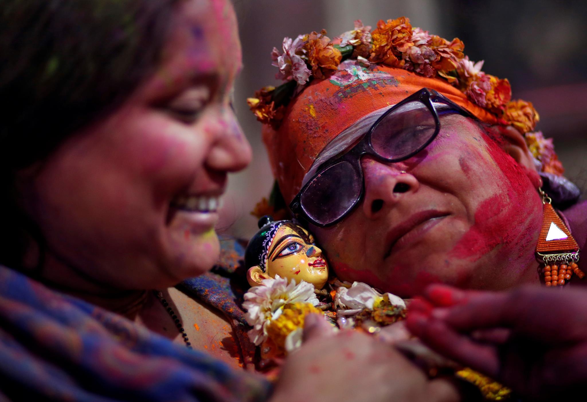 Mulheres seguram uma representação da deusa hindu Radha durante o Festival das Cores