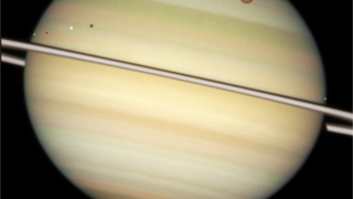 Várias luas de Saturno em trânsito no planeta. Titã está à direita e tem uma cor laranja NASA/ESA