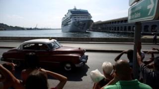 Um carro com turistas passa junto ao porto de Havana, com um navio de cruzeiro ao fundo
