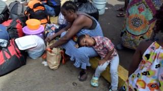 Uma mulher dos Camarões e o seu filho aguardam com outros migrantes no exterior dos serviços de migração em Tapachula