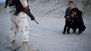 Uma migrante guatemalteca e o seu filho detidos por um soldado da Guarda Naciona mexicana