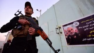 Membro do grupo xiita iraquiano em frente a obituário de Qassem Soleimani