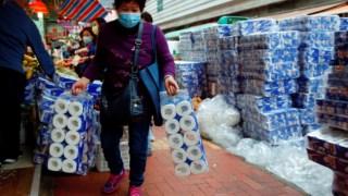 Uma senhora compra papel higiénico num supermercado em Hong Kong