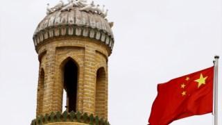 Uma bandeira chinesa junto à antiga mesquita de Id Kah, na cidade velha de Kashgar, em Xinjiang