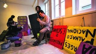 Voluntários e elementos do movimento Que se Lixe a Troika pintam cartazes no espaço MOB